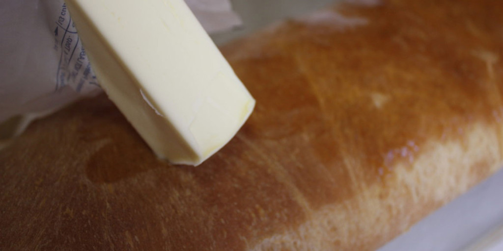 butter being rubbed on the top crust of the sandwich bread