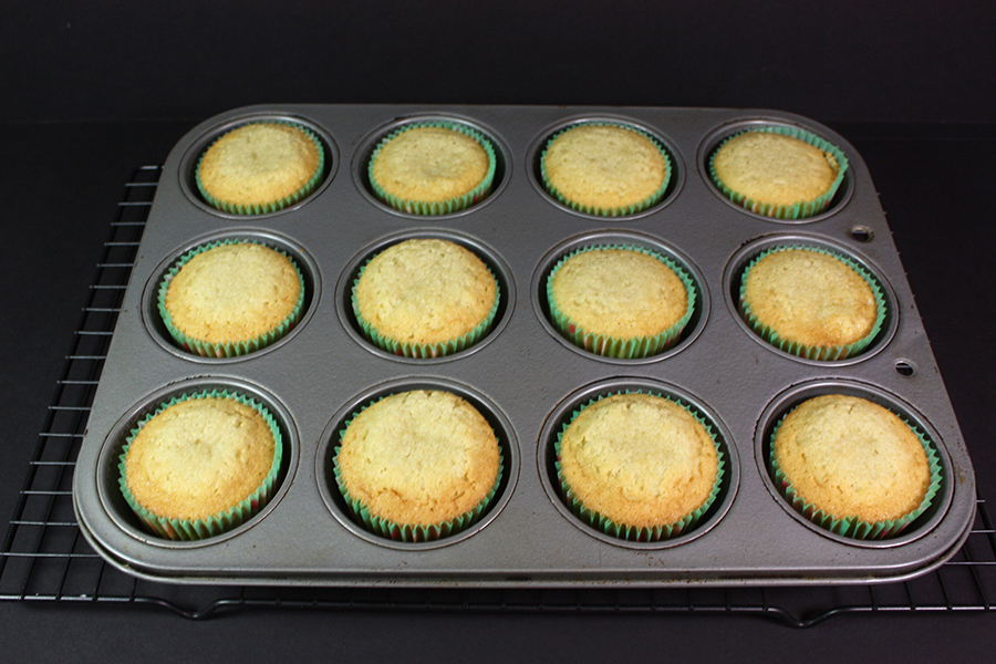 baked coconut cupcakes in the muffin pan on a wire rack