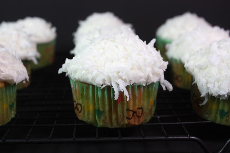 frosted Coconut cupcakes on a wire rack