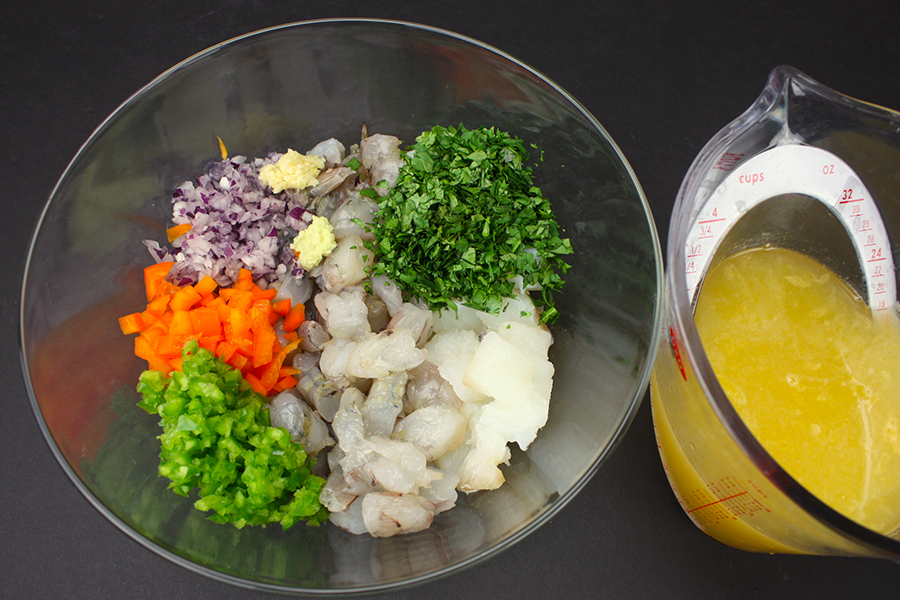 ceviche ingredients in a glass bowl next to the marinade ingredients in a measuring cup