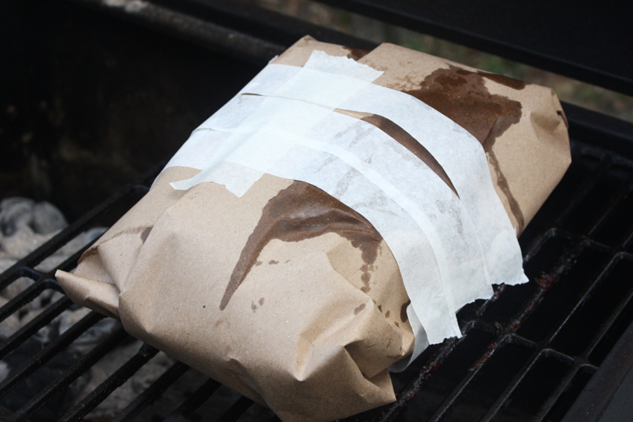 Smoked Pork Shoulder wrapped in butcher paper on the grill