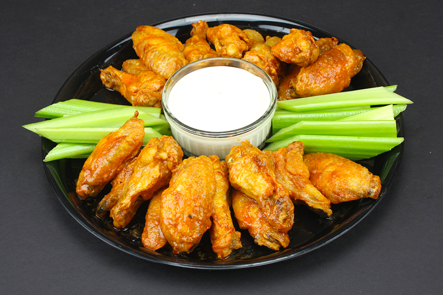 Crispy Oven Baked Chicken Wings on a round black platter with celery sticks and blue cheese dip