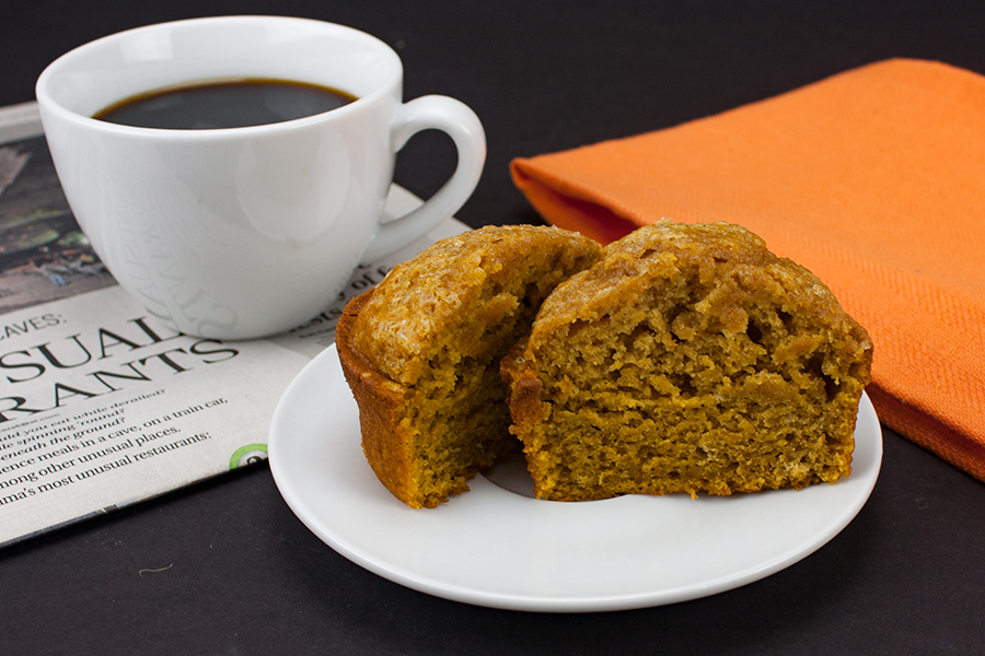 Bakery Style Pumpkin Muffin sliced in half on a white plate next to a white coffee mug