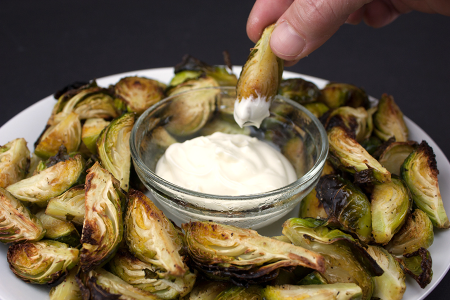 Roasted Brussel Sprouts with Aioli Dipping Sauce on a white platter with sauce in a ramekin in the middle