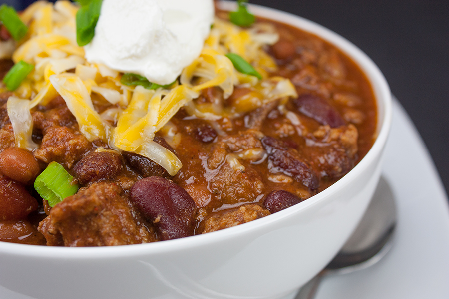 Chili with cheese and sour cream in a white bowl