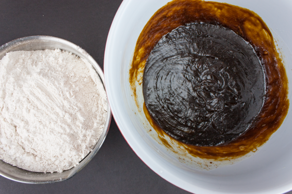 molasses cookie wet ingredients in a bowl next to dry ingredients in another bowl