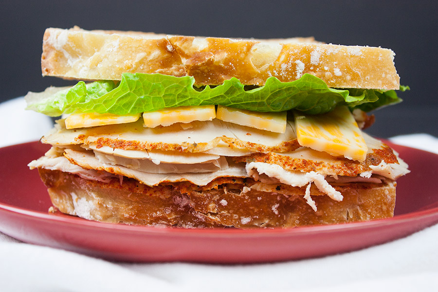Homemade Cajun Turkey Deli Meat made into a sandwich on a red plate