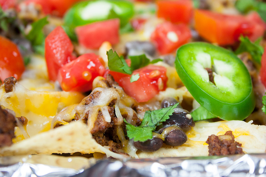 A closeup of a nacho with jalapenos and tomatoes