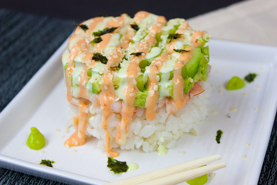Spicy Shrimp Sushi Stack drizzled with sauces on a square white plate with chopsticks