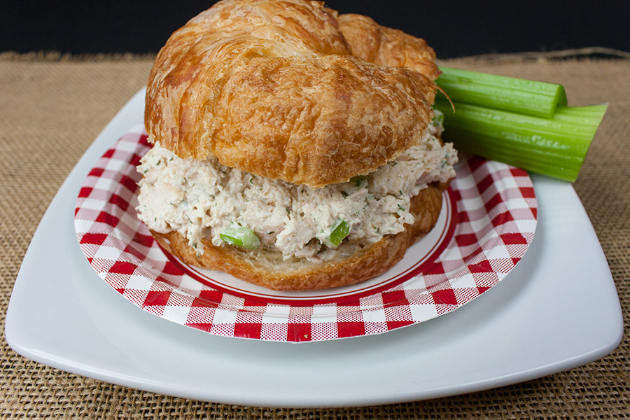 Savory Chicken Salad in a croissant on a white and red checked plate