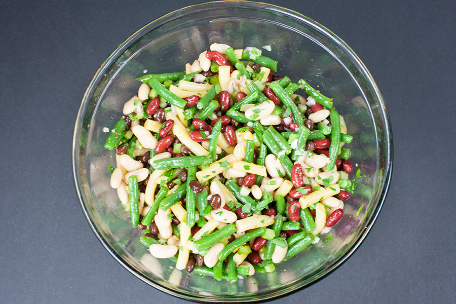Five Bean Salad ingredients tossed with the dressing in a glass mixing bowl