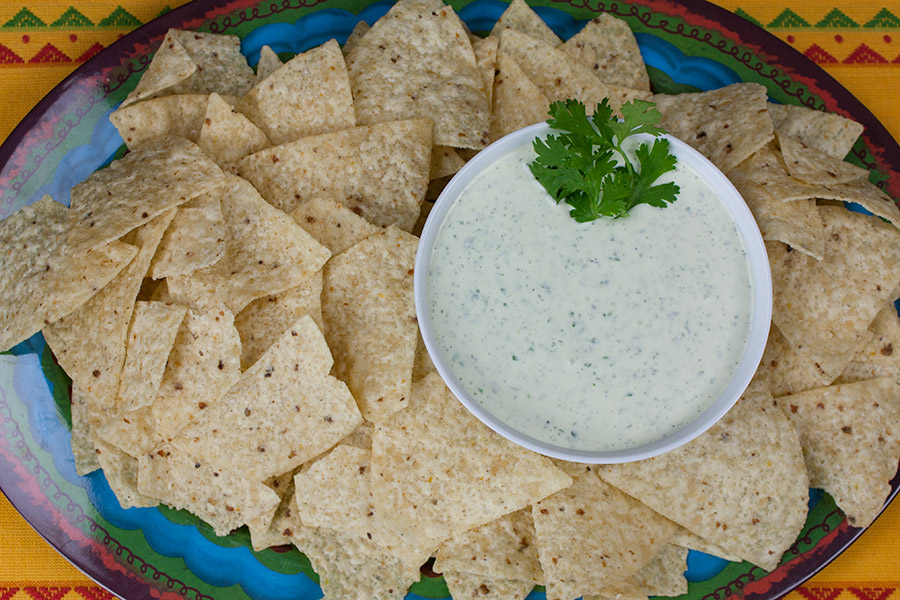 Creamy Jalapeno Cilantro Dip in a white bowl surrounded by tortilla chips