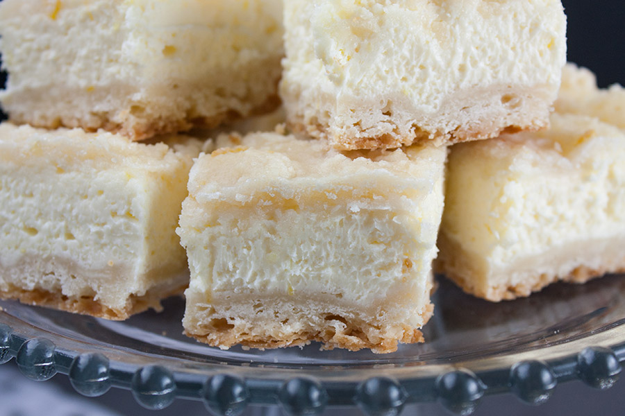 Lemon Cheesecake Shortbread Bars stacked on a glass cake stand