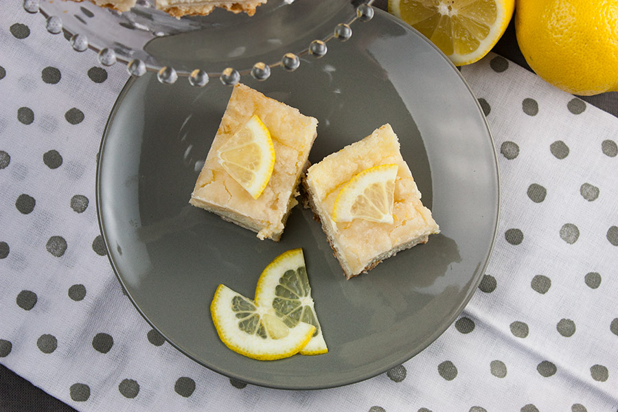 Lemon Cheesecake Shortbread Bars on a gray plate garnished with lemon slices