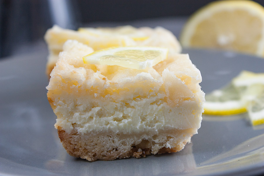 closeup of the Lemon Cheesecake Shortbread Bars on a gray plate
