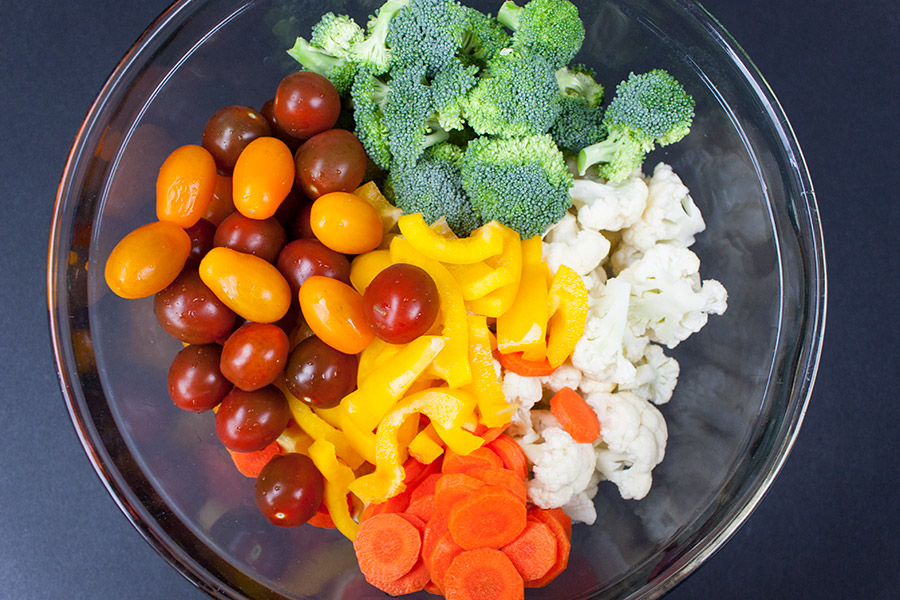 marinated fresh vegetable salad - tomatoes, broccoli florets, chopped bell peppers, diced carrots, and cauliflower florets in glass bowl