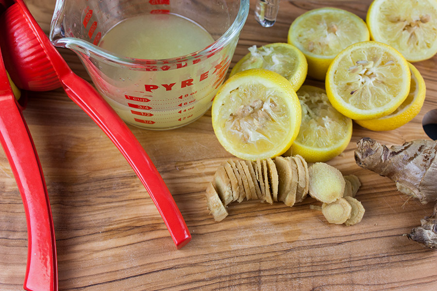 Honey Ginger Lemonade - juiced lemons, slice ginger and a measuring cup on a wooden cutting board