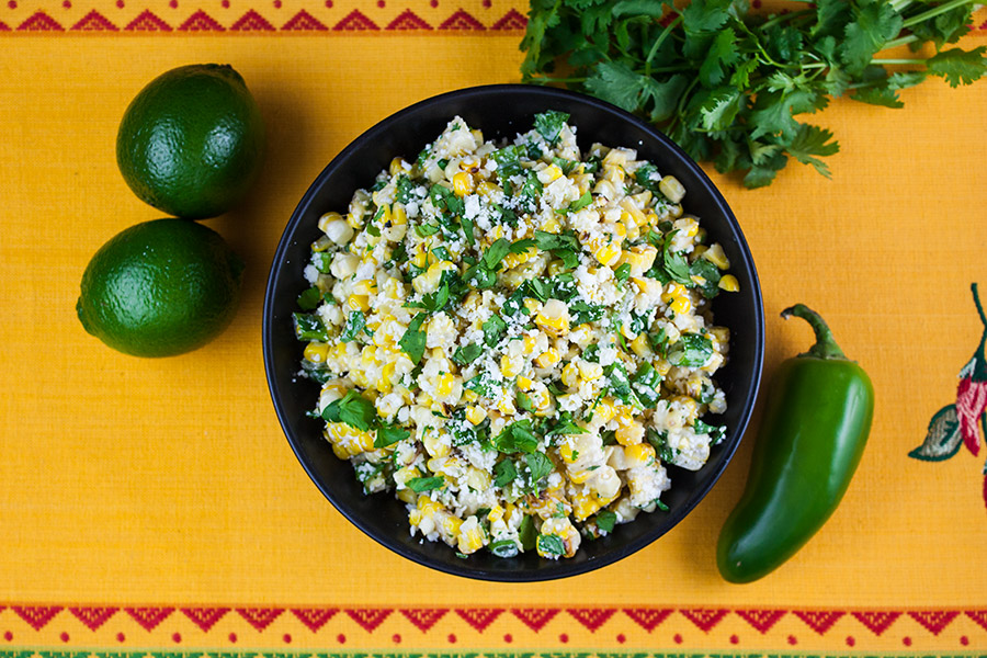 Grilled Mexican Street Corn Salad in a black bowl on a yellow back ground