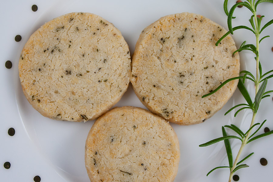Savory Parmesan Rosemary Shortbread on a white plate garnished with fresh rosemary sprig