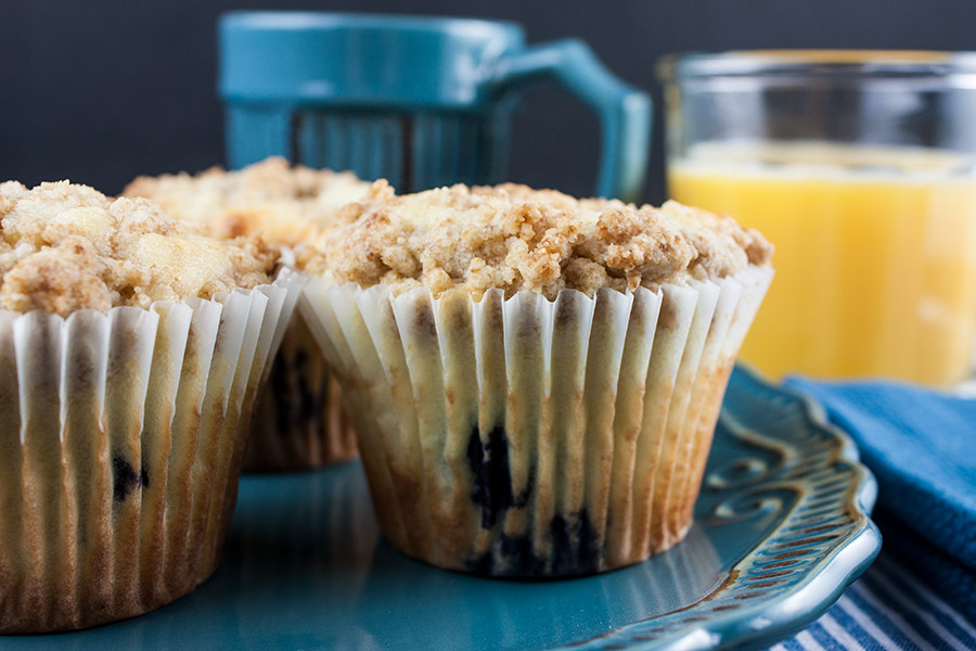 Lemon Streusel Blueberry Muffins on blue plate blue coffee mug orange juice in clear glass