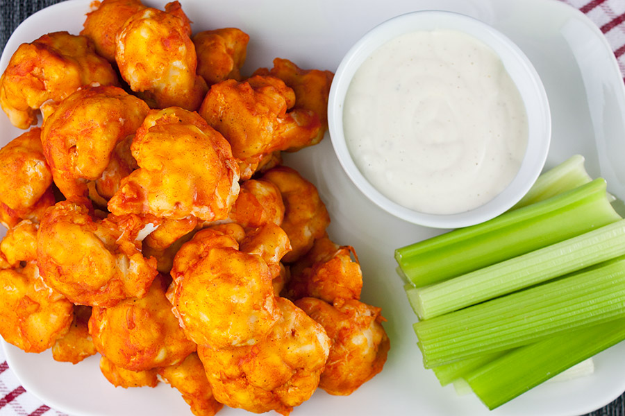 Baked cauliflower bites on a white platter with celery