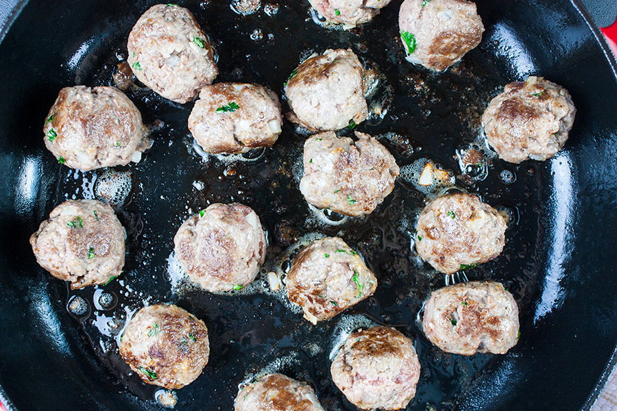 Swedish meatballs browning in a cast iron skillet