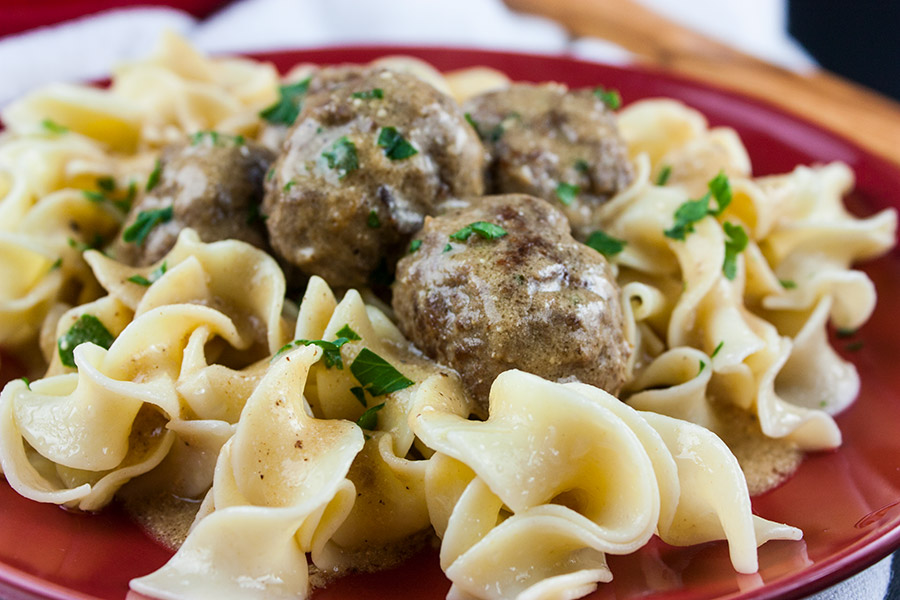 Swedish Meatballs over egg noodles on a red plate