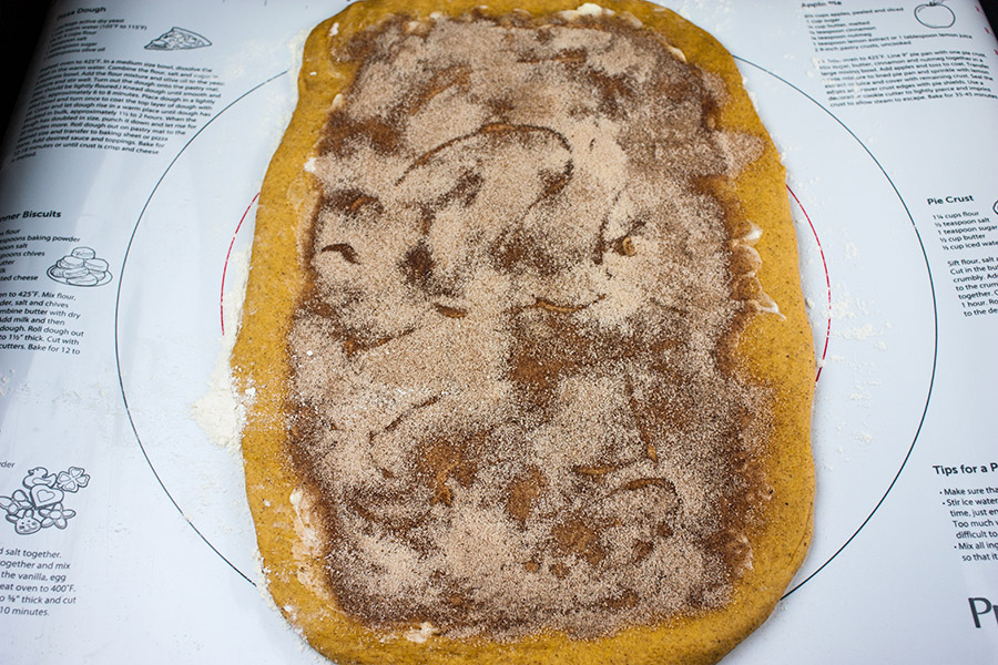 pumpkin cinnamon swirl bread dough rolled out on a pastry mat with filling spread on the middle