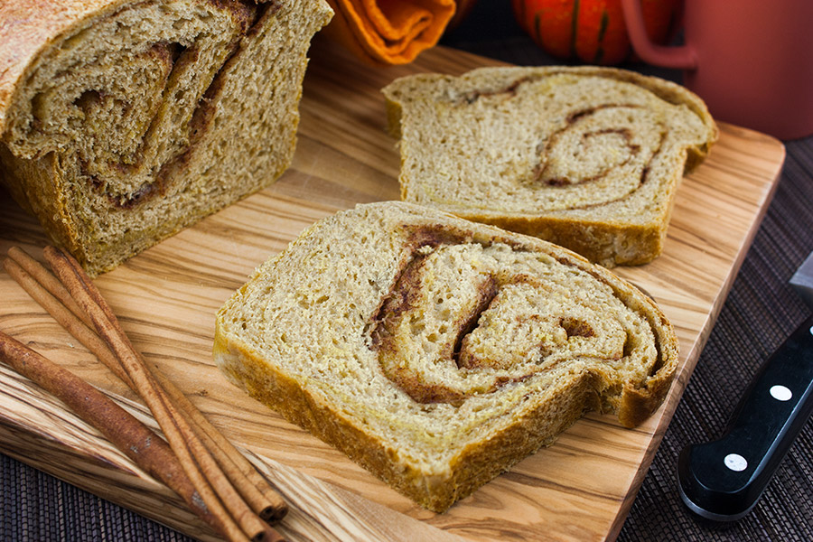 Pumpkin Cinnamon Swirl Bread loaf sliced on a wooden cutting board