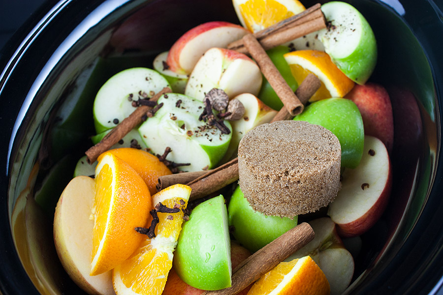 slow cooker apple cider - apples, orange, cinnamon sticks and spices in the crock of a slow cooker