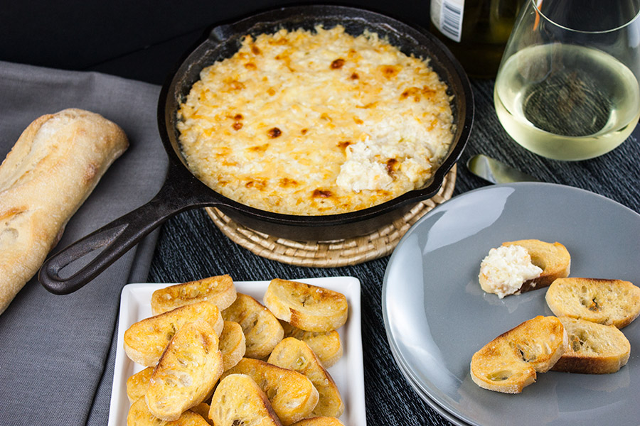 Baked Vidalia Onion Dip in a cast iron skillet with toasted baguette slice on a gray plate