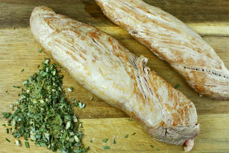 Tuscan Pork Tenderloin - seared loin and chopped herbs on a wooden cutting board