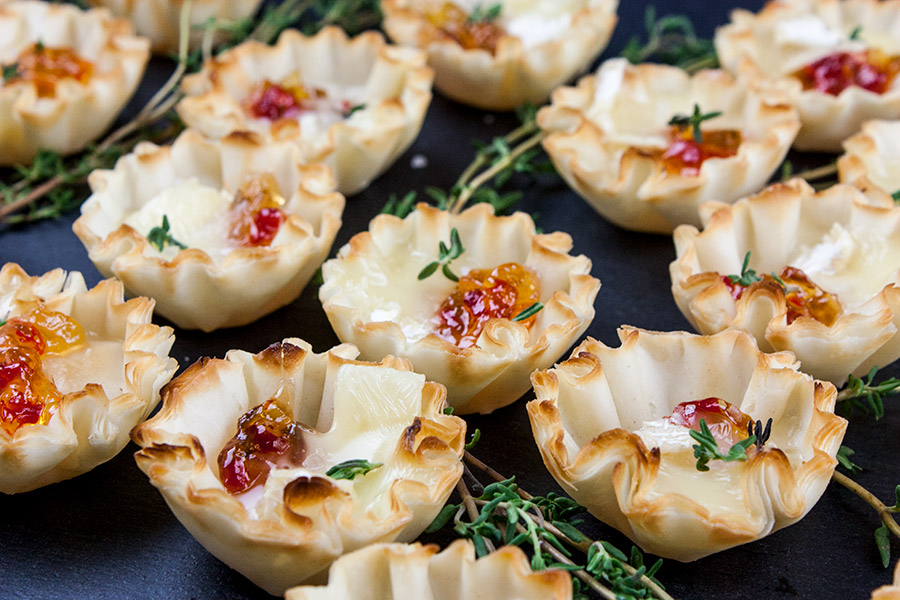 close up of Pepper Jelly Brie Bites on a black slate garnished with fresh thyme
