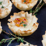 close up of pepper jelly brie bite on slate with fresh thyme sprig garnish