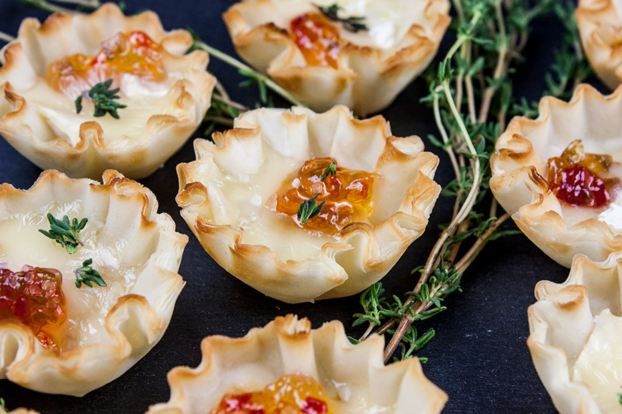 closeup of Pepper Jelly Brie Bites on a black slate garnished with fresh thyme