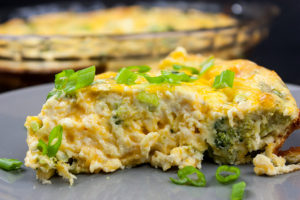 slice of crustless broccoli cheddar quiche on gray plate garnished with diced green onions