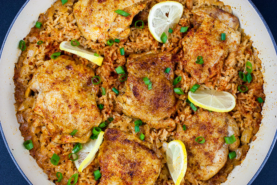 One Pan Spanish Chicken and Rice - cooked in the skillet garnished with lemons slices and green onions