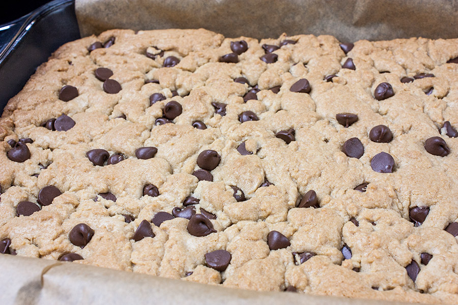Chocolate Chip Cookie Bars - baked cookie dough in parchment lined baking pan