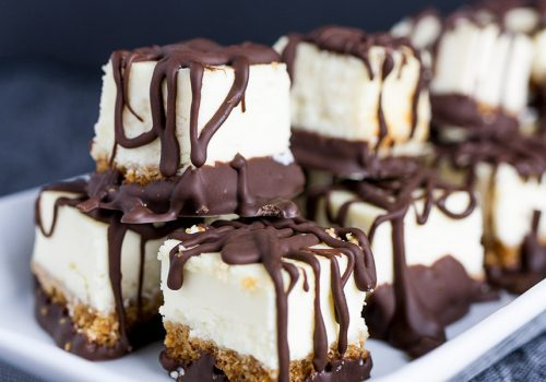 Chocolate Covered Cheesecake Bites - An easy ultimate party treat! A cool, creamy, rich mini cheesecake bite drizzled with chocolate. Perfect for barbecues, holidays or parties of any kind!