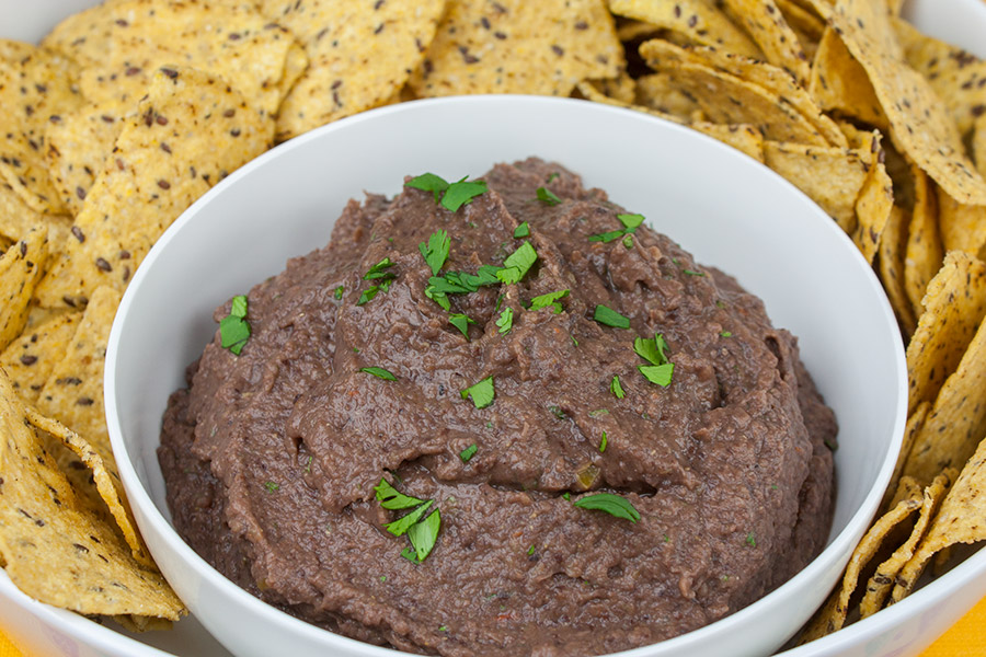 Easy Black Bean Dip - dip in a bowl garnished with cilantro surrounded by tortilla chips
