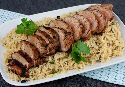 Grilled Adobo Pork Tenderloin - Sliced pork tenderloin on a bed of cilantro lime rice