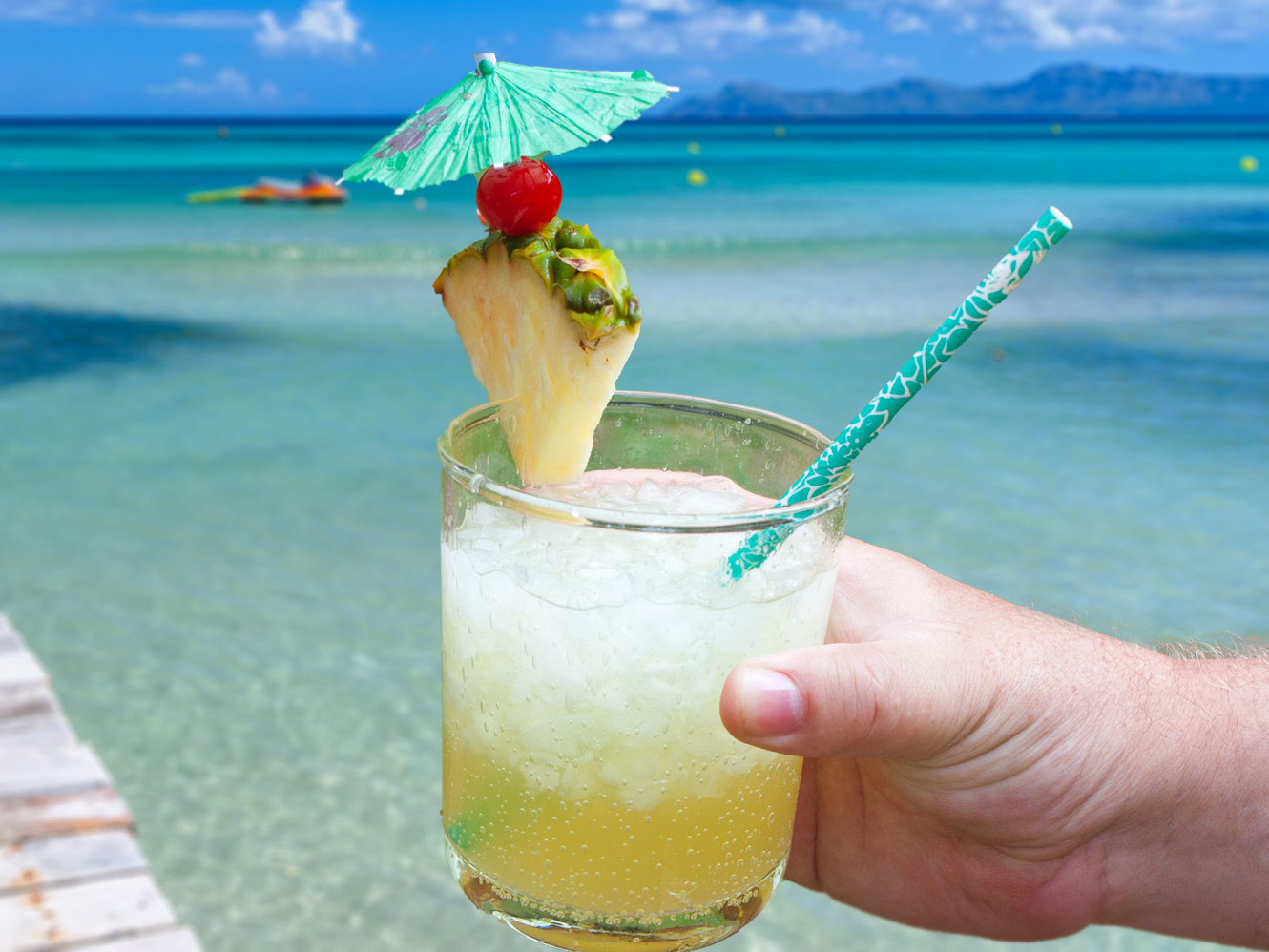 Jamaican Me Crazy Cocktail in a clear glass garnished with pineapple, cherry, umbrella and straw with an ocean background