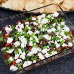 Easy Mediterranean Dip - Layered with hummus, sour cream, tomato, cucumber, roasted red pepper, feta cheese, Kalamata olives and green onions. Perfect for any party or gathering!