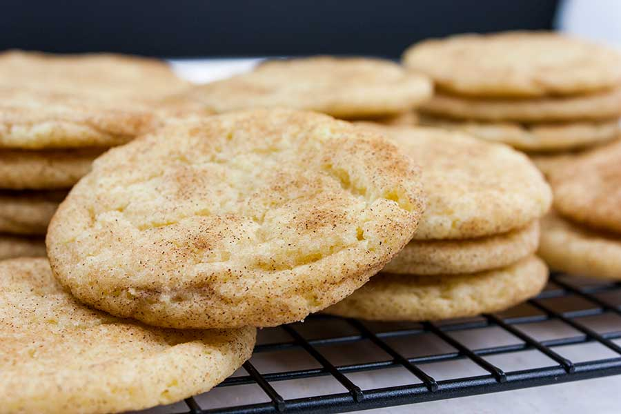The Best Chewy Snickerdoodle Cookies - baked cookies stacked on a wire cooling rack