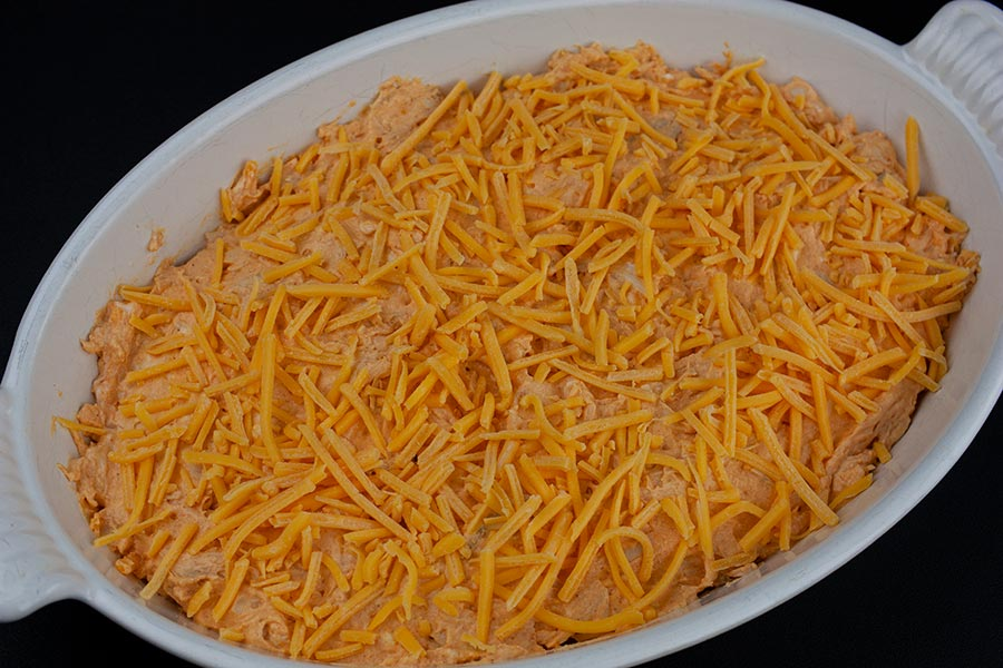 Buffalo Chicken Dip - unbaked dip in a white casserole dish topped with cheddar cheese