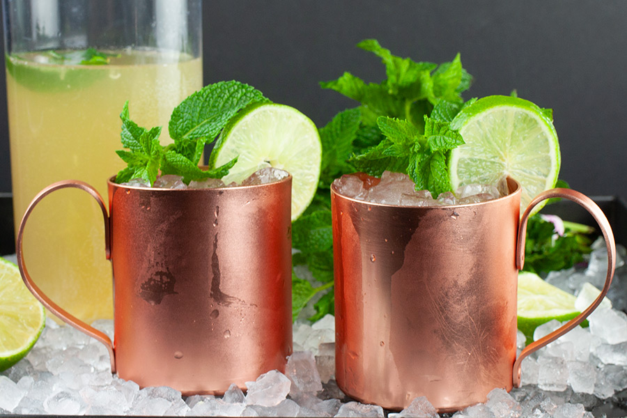 Skinny Moscow Mule in 2 copper mugs garnished with a lime slice and fresh mint leaves