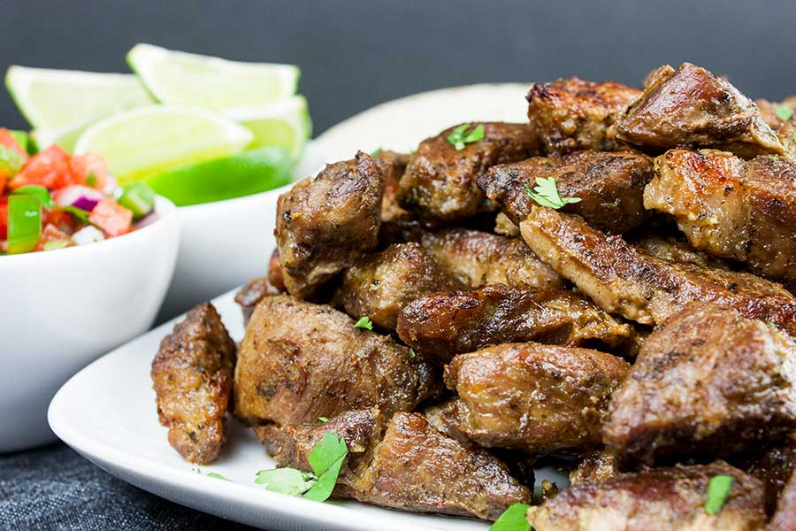 Crispy Pork Carnitas - Slow oven roasted marinated pork cubes with a crispy caramelized crust. Rich, moist, flavorful and so tender it melts in your mouth!