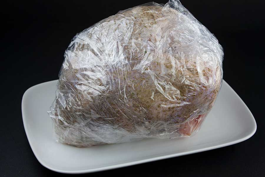 Smoked Turkey Breast - turkey breast wrapped in plastic on a white platter
