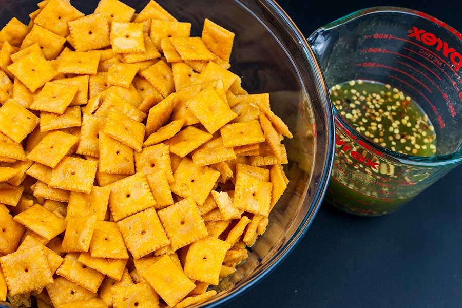 Firecracker Cheez-Itz - crackers in a large glass bowl with seasoning mixture in a glass measuring cup next to it