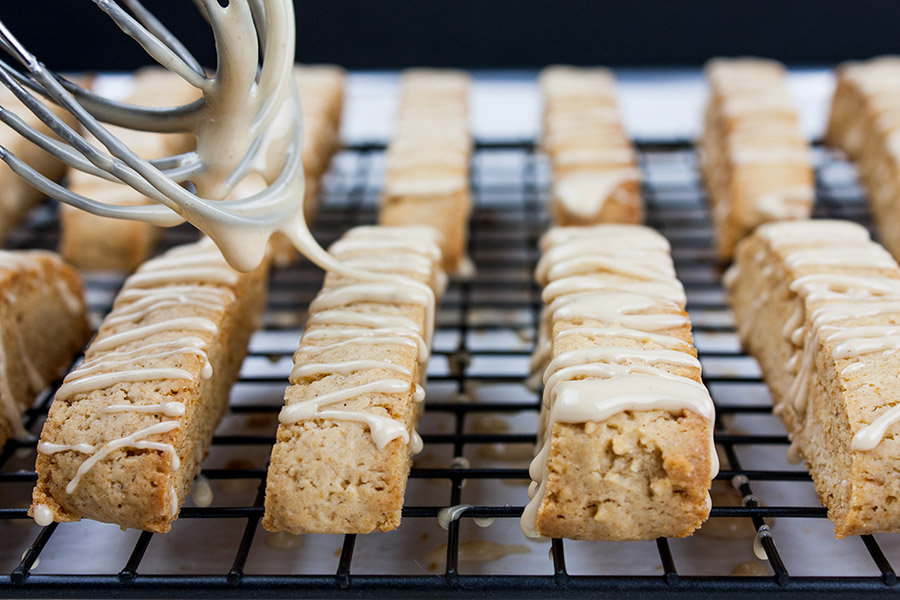 Spiced Apple Cider Biscotti - glaze being drizzled over baked biscotti
